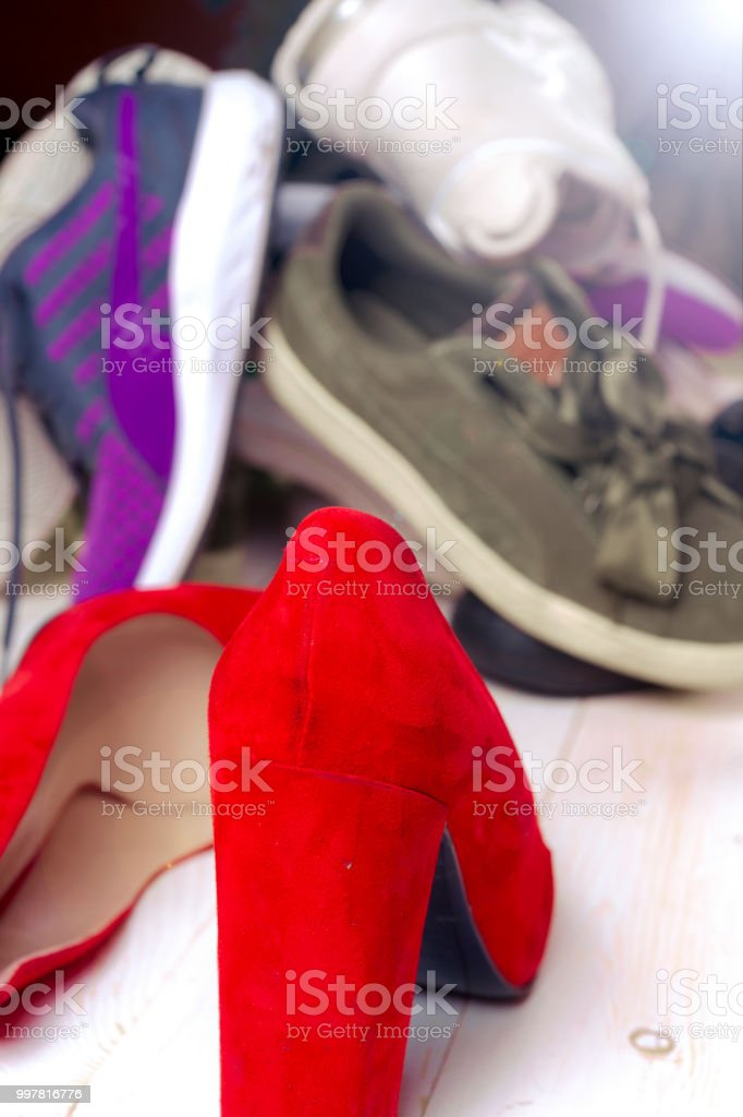 f0b5a017d63c Big heap of different sports shoes and red high heel women s shoes on white  background. - Stock image .