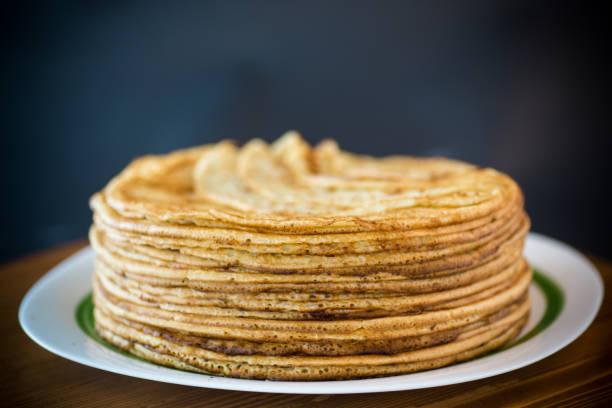 hohen bigstack dünne pfannkuchen in einer platte - schmaler tisch stock-fotos und bilder