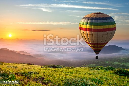 Big hot air baloon over idyllic landscape with green grass covered morning mountains with distant peaks and wide valley full of thick white cloudy fog.