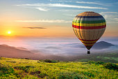 istock Big hot air baloon over idyllic landscape with green grass covered morning mountains with distant peaks and wide valley full of thick white cloudy fog. 1284120860