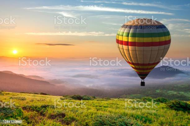 Photo of Big hot air baloon over idyllic landscape with green grass covered morning mountains with distant peaks and wide valley full of thick white cloudy fog.