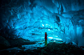 Woman exploring glacial ice cave.
