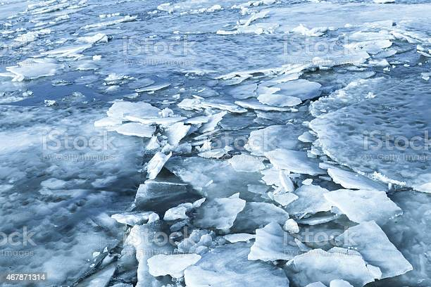 Photo of Big ice fragments covered with snow on frozen river