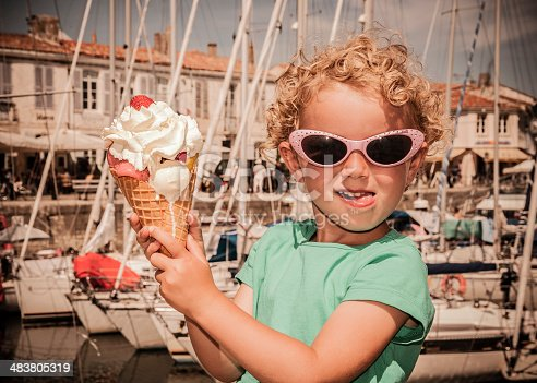 Child holding a really big ice-cream.