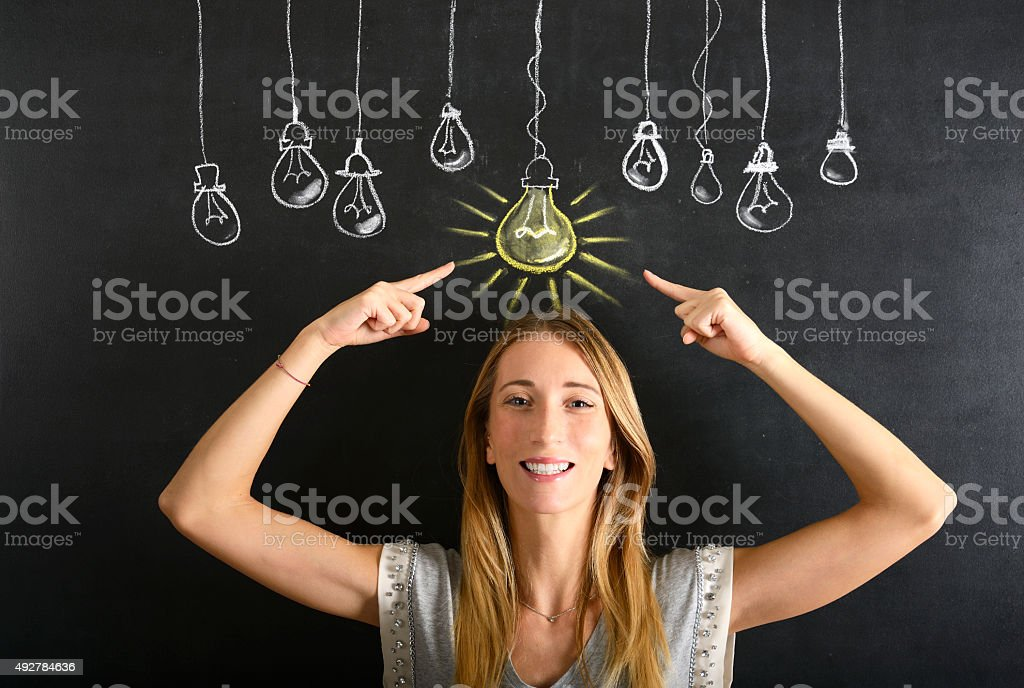 Big idea concept Young businesswoman pointing a big glowing light bulb sketched on blackboard 20-29 Years Stock Photo