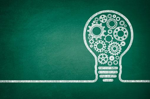Big idea light bulb with gears on green chalkboard