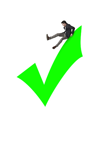 Shot of a businessman on top of a green check mark against a white background