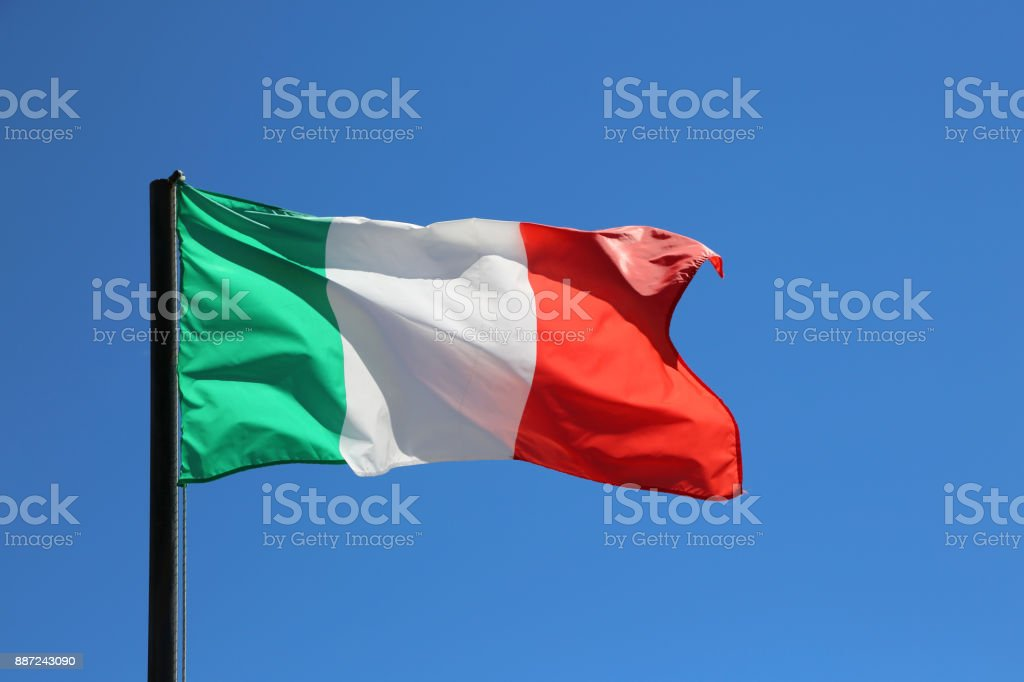 Gran bandera italiana ondeando en el cielo azul - foto de stock