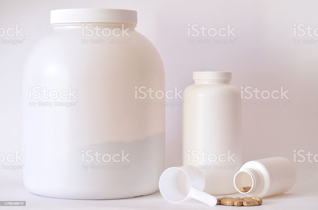 Big jar of protein powder, bottles and scoop stock photo