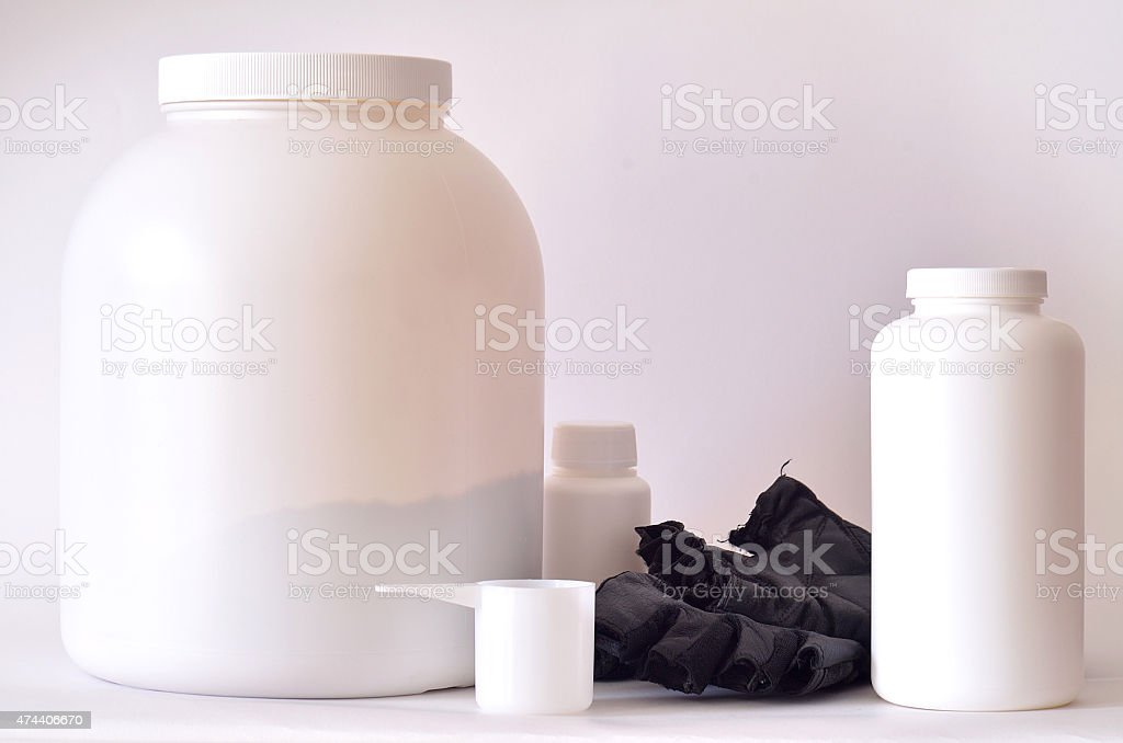 Big jar of protein powder, bottles and shaker stock photo