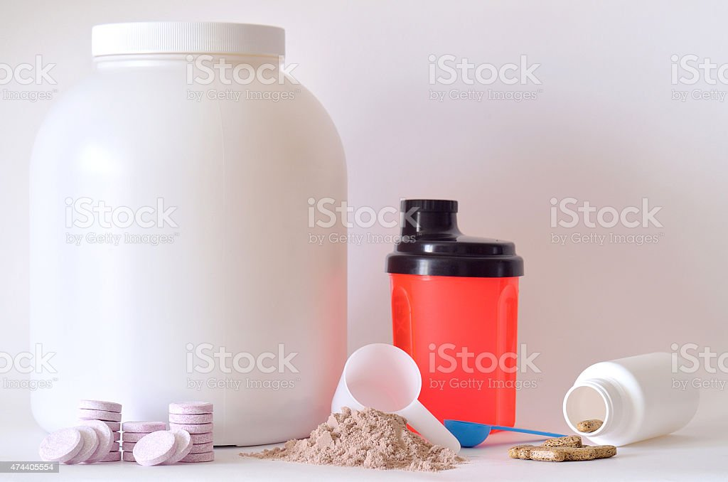 Big jar of protein powder, shaker, pills and tablets stock photo