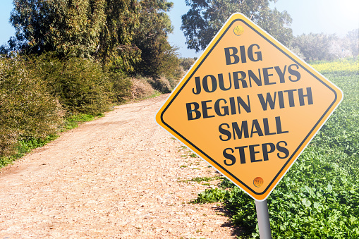 Big Journeys Begin With Small Steps sign on road