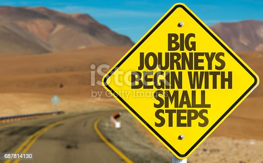 istock Big Journeys Begin With Small Steps sign with sky background 687814130