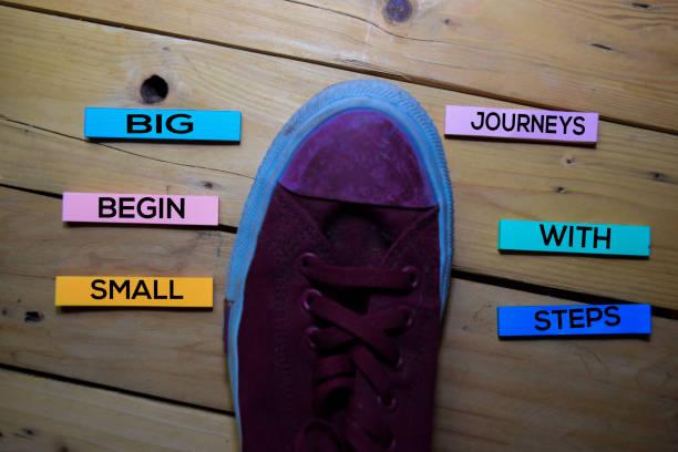 big journeys begin with small steps text mit sneaker auf klebrigen notizen isoliert auf tisch tisch hintergrund - bedeutungsvolle zitate stock-fotos und bilder
