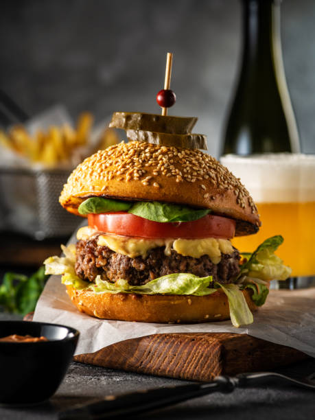 Cтоковое фото Big juicy delicious cheeseburger with beef, tomato, lettuce and pickles. Burger with beer and french fries