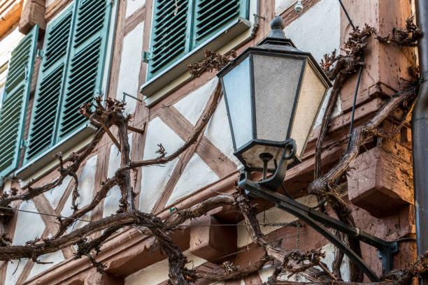 Große Lampe an einem alten historischen Gebäude und grüne Fensterläden – Foto