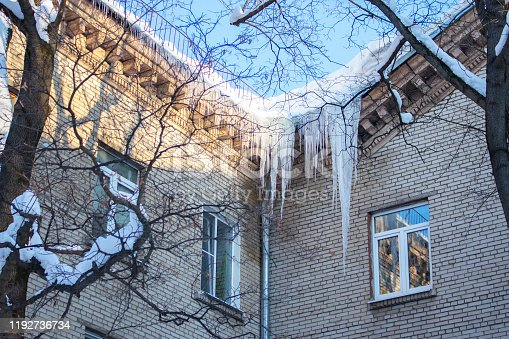 Big long icicles hanging from the roof of a residential building, winter ice cold snow nature. Freezing ice water at the corner of a brick apartment building, danger