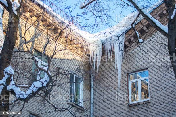 Photo of Big long icicles hanging from the roof of a residential building, winter ice cold snow nature. Freezing ice water at the brick apartment building, danger