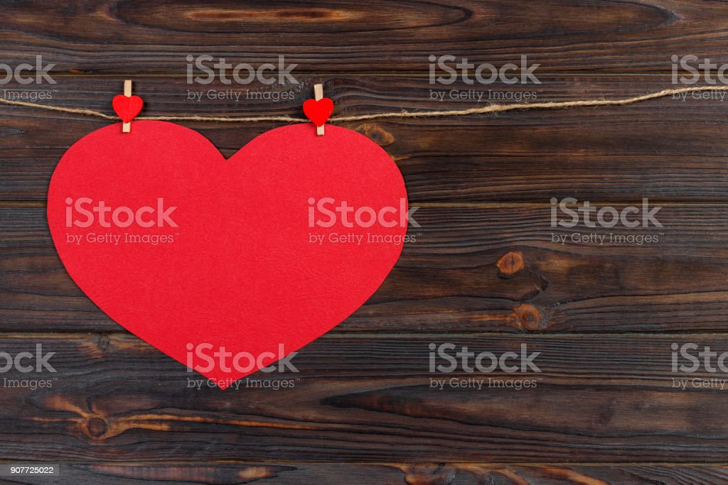 Big love red heart hanging on wooden texture background, valentines day card concept stock photo