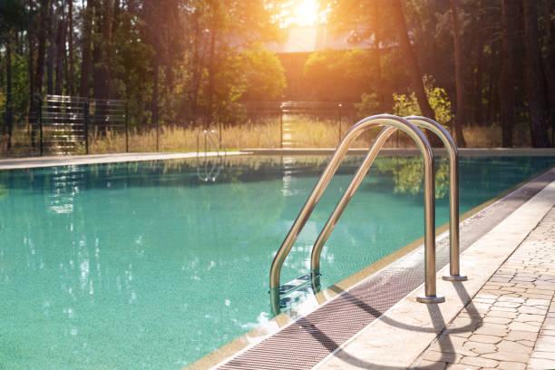 duży luksusowy pusty prostokątny basen z czystą niebieską wodą i drabiną w tropikalnym leśnym kurorcie na plaży o wschodzie słońca rano i nikt na zewnątrz. zdrowy wypoczynek w podróży i ćwiczeniach - staw woda stojąca zdjęcia i obrazy z banku zdjęć