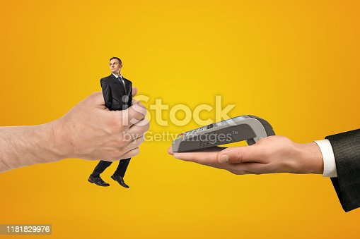 945598452 istock photo Big male hand passing tiny businessman to another hand with PIN pad on yellow background 1181829976