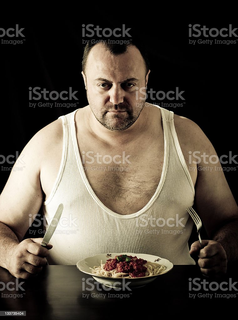 Big man eating spaghetti stock photo