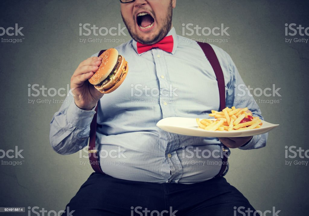 big man in formal clothes sitting and consuming plate with fast food stock photo