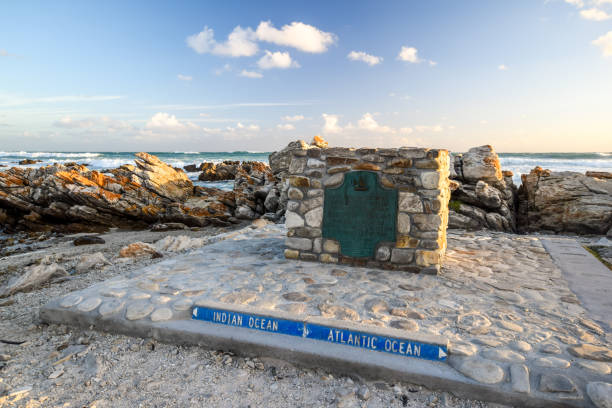 Big marker stone at Cape Agulhas(Cape of the Needles),South Africa,southernmost point of the African continent.It marks the division point between the Atlantic and Pacific Ocean. Big marker stone at Cape Agulhas(Cape of the Needles),South Africa,southernmost point of the African continent.It marks the division point between the Atlantic and Pacific Ocean. headland stock pictures, royalty-free photos & images