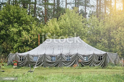 Big military field tent with windows and a stove on the lawn in the forest