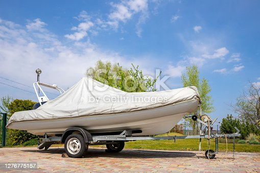 Big modern inflatable motorboat ship covered with grey or white protection tarp standing on steel semi trailer at home backyard on bright sunny day with blue sky on background. Boat vessel storage.