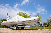 istock Big modern inflatable motorboat ship covered with grey or white protection tarp standing on steel semi trailer at home backyard on bright sunny day with blue sky on background. Boat vessel storage 1276775157