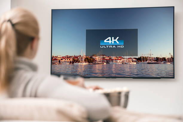 big modern tv with 4k resolutions and young woman on foreground watching some video - televisor imagens e fotografias de stock