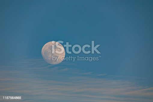 Big moon at sunset with light clouds at blue sky