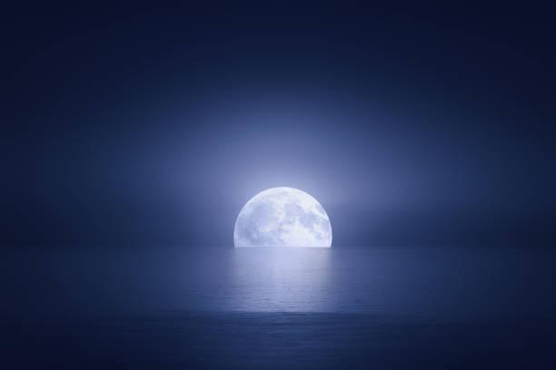 big moon over the sea at night stock photo