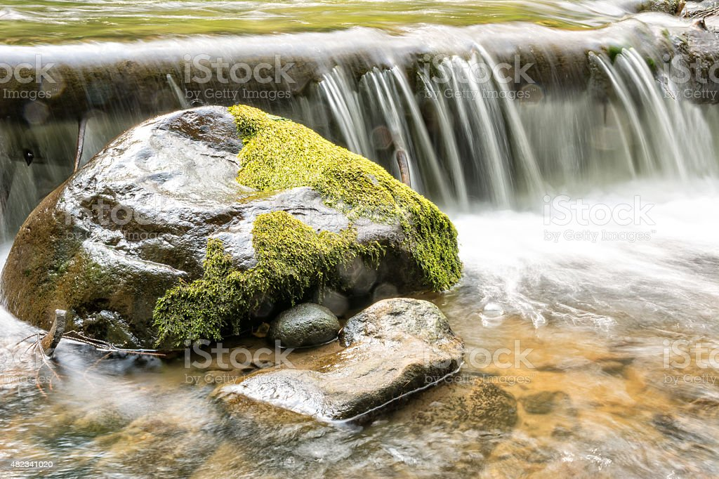 Big mossy boulder in clear water of mountain river stock photo