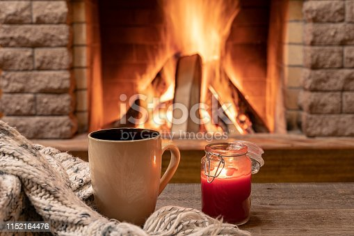 istock Big mug with hot tea, and a candle , wool scarf, near cozy fireplace, hygge, home sweet home. 1152164476