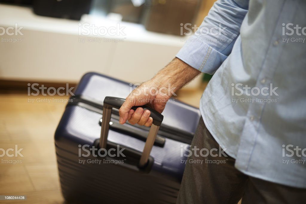 Big blue travel suitcase being held by an unrecognizable elderly...