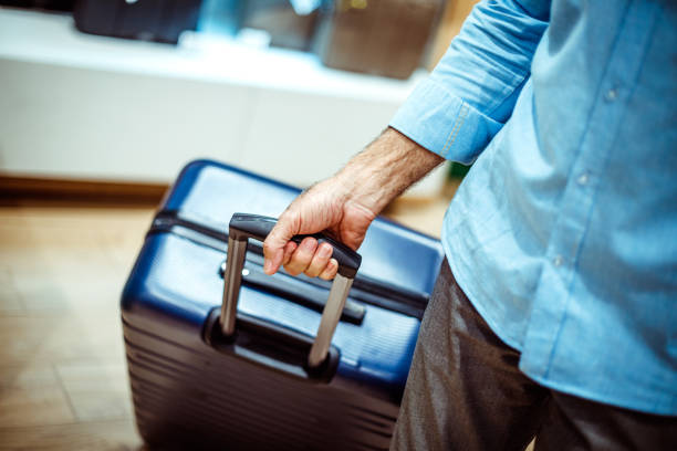 Big navy blue travel suitcase being held by an unrecognizable person in a bags and accessories store stock photo