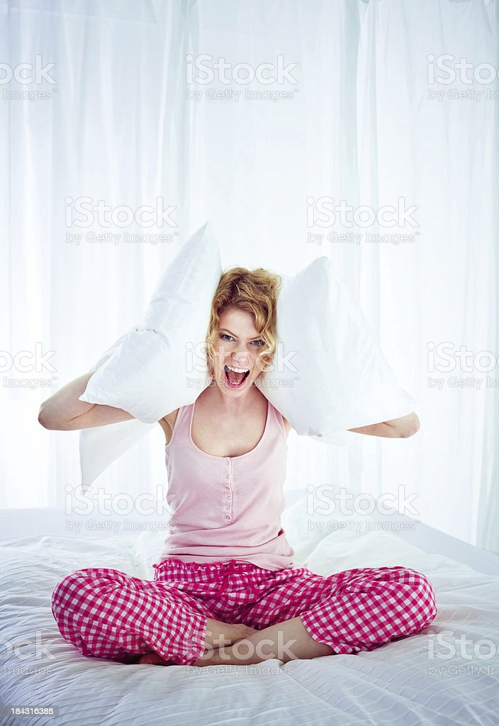Big noise in the early morning Screaming young adult woman sitting on a bed and squeezes pillows to her ears, can't sleep because of a big noise. 25-29 Years Stock Photo