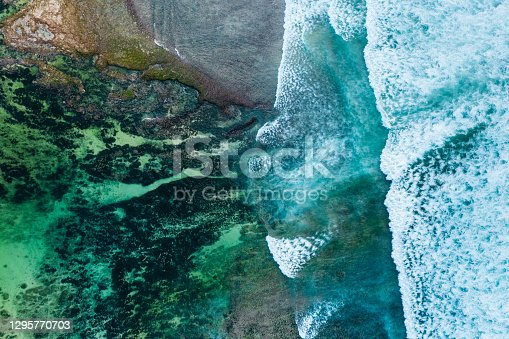 istock Big ocean waves hitting a coral reef. View from above. 1295770703
