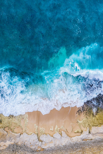 Big ocean waves hitting a rocky beach. View from above.