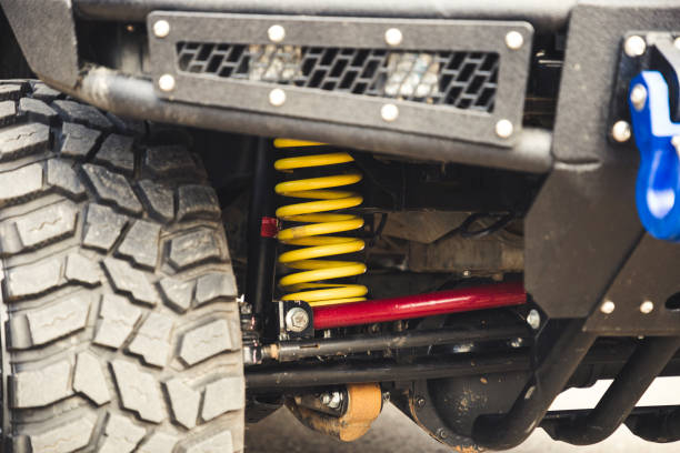 big off road car coil spring. yellow shock absorber on the car. - molla foto e immagini stock