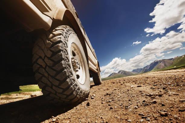 roda de carro offroad grande na estrada do país - estrada em terra batida - fotografias e filmes do acervo