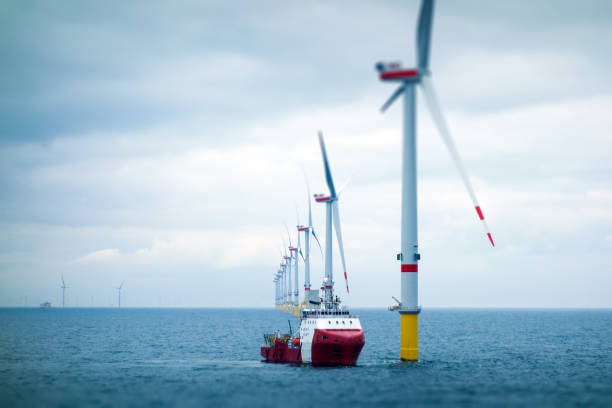 Big Offshore wind-farm with transfer vessel Wind-turbine, offshore, worker, boat, sea, sun, vessel windmill stock pictures, royalty-free photos & images