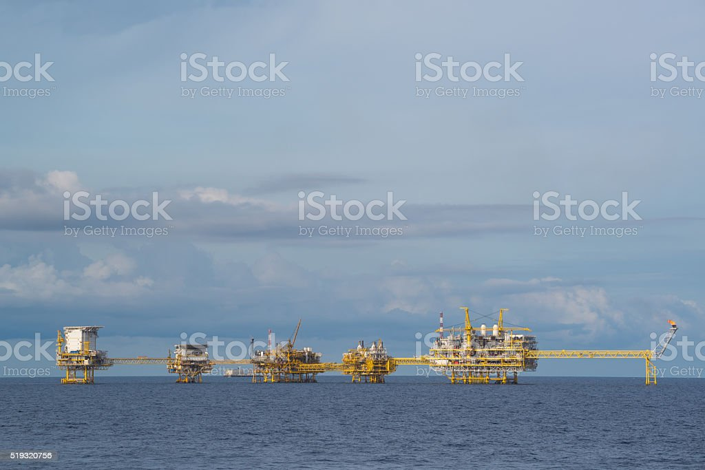 Big oil and gas production platfrom in ocean with cloud and blue sky