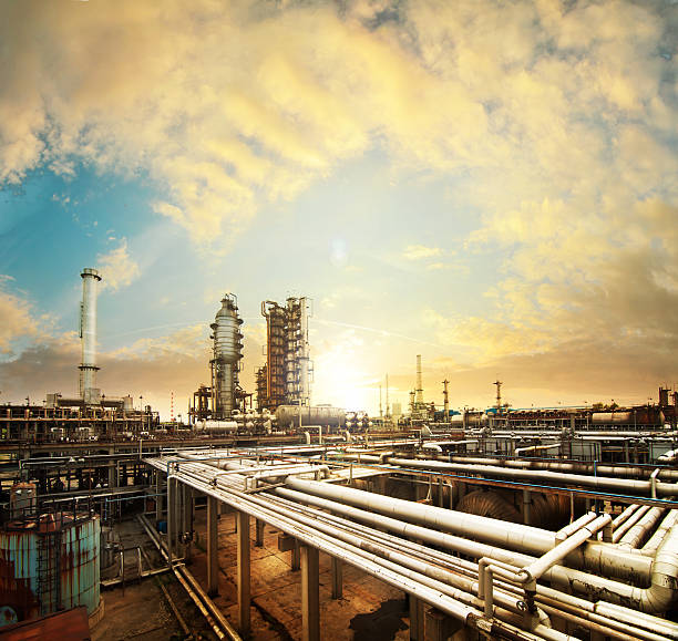 big oil refinery in a sunset - refinery stock photos and pictures