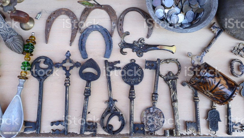 Grandes chaves velhas e ferraduras no balcão de uma loja de antiguidades - foto de acervo