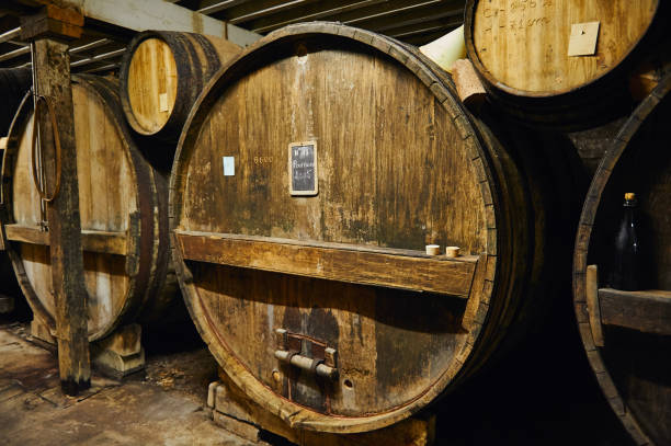 Big old oak casks of pommeau of calvados in a cellar Old oak casks with ageing traditional apple beverage of pommeau in a distillery cellar in Calvados region, Normandy, France calvados stock pictures, royalty-free photos & images