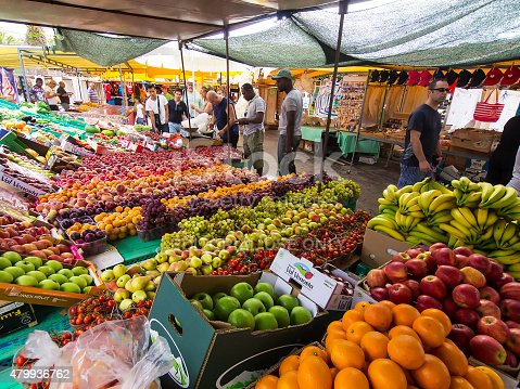 Marsaxlokk, Malta - May 31, 2015: Sunday day at big Marsaxlokk market with many different fruits and vegetables protected from sun with big tarpaulins. In background are people walking by kiosks while some of them are looking at offered merchandise