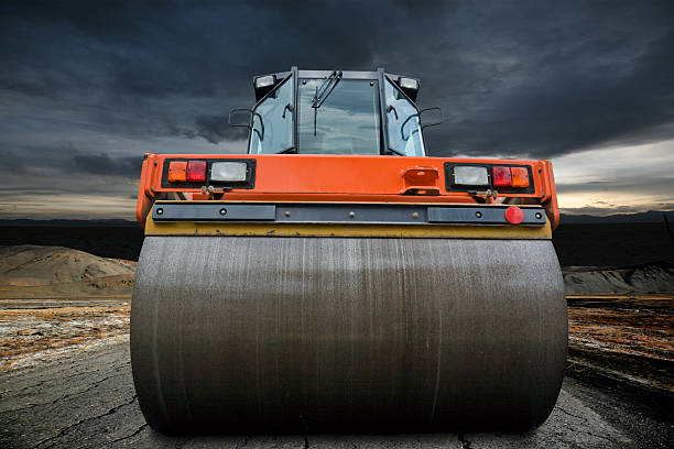 Big orange road roller upon a cloudy sky stock photo